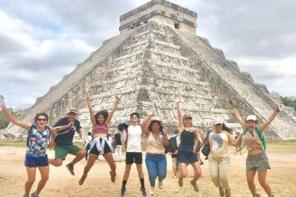 Students jumping with excitement in front of Chichen Itza