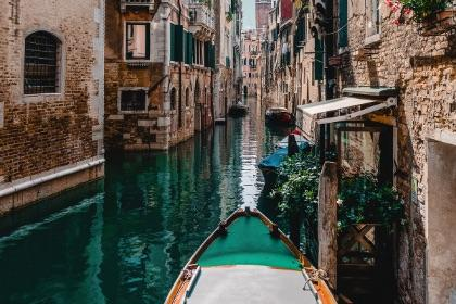 View looking over the front of a boat in a canal in Venice