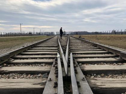 Taken during a moment of reflection at the most horrific Nazi extermination camp, Auschwitz, where millions of Jews were trained in one way by cattle car alive, but were murdered before being able to take the other side of the train tracks home
