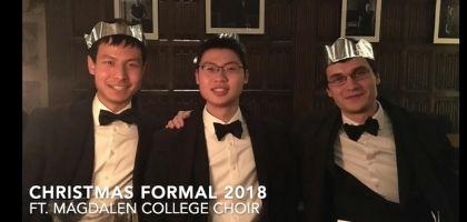 Image of three students posing in formal suits at Christmastime
