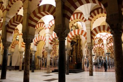 The arches of the beautiful Mezquita-Catedral of Córdoba, one of the best places to see the intersection of the three cultures (Islam, Christianity, and Judaism) that define the city's history.