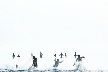 People running into the ocean in Sweden.